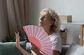 Stressed middle aged retired woman using paper fan.