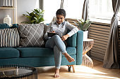 Indian young woman using computer tablet, sitting on cozy sofa