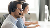 Confident call center operator agent in headset consulting client online