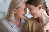Happy older mother and adult daughter touching foreheads, feeling love