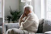 Lonely old man sitting on couch lost in pessimistic thoughts