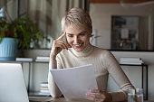 Smiling Caucasian businesswoman read good news in paper document
