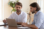 Confident male colleagues cooperate at laptop at meeting