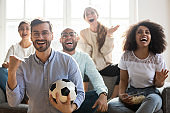 Excited multiracial young people cheering team watching football online