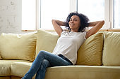 Peaceful African woman resting on couch in modern living room