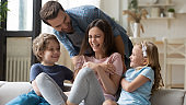 Overjoyed family with small kids play at home