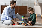 Happy father and little son playing with toys together