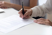 Close up view female hand signing contract legal document