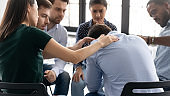 Rear view diverse people comforting frustrated depressed man at meeting