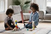 African kids play with dinosaurs and wooden blocks at home