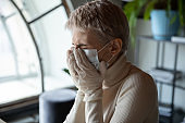 Stressed female employee got infected by coronavirus, suffering from symptoms.