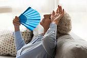 Exhausted older woman feeling unwell, suffering from heat, waving fan
