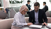 Happy middle aged woman signing document meeting with broker, insurer