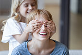 Close up cute daughter making surprise covering eyes to smiling mom.