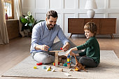 Happy father playing with little son on warm floor