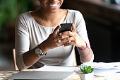 Smiling biracial woman hold cellphone chatting online