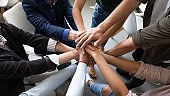 Top view hands stacked together as symbol of teambuilding