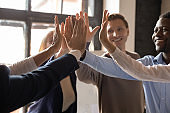 Closeup different ethnicity businesspeople raised hands giving high five