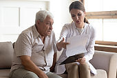 Female caregiver explain insurance contract to male senior patient