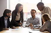 Happy diverse colleagues have fun brainstorming at meeting