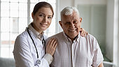 Young female professional gp embracing shoulders of smiling retired patient.