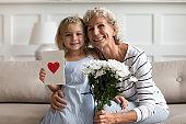 Little granddaughter congratulates mature grandmother presents her flowers and postcard