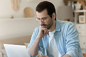 Pensive Caucasian man look at laptop screen working on gadget