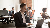 Smiling support service employee consulting client on phone, using laptop