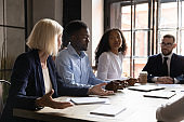 Diverse team listening aged leader during group meeting in boardroom