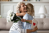 Granddaughter congratulates grandmother at birthday gave her postcard and flowers