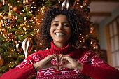 Head shot portrait smiling African American woman showing heart gesture
