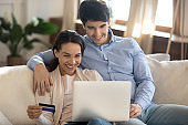 Smiling young family couple shopping at internet store using laptop