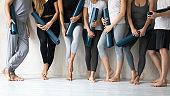 People wearing sportswear holding mats waiting yoga class