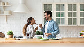 Happy loving couple singing, having fun with kitchenware in kitchen
