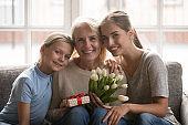 Happy three generation family celebrating grandmothers birthday portrait.