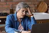 Stressed senior woman have problems working on laptop