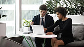 African american businesswoman consulting client showing business plan on laptop