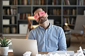 Exhausted tired businessman with stickers on eyes sleeping at workplace