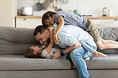 Happy father playing with two little kids at home