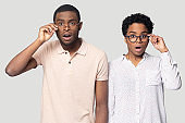 Confused african couple gawp at camera open mouth lowering glasses