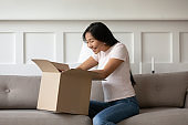 Asian woman sitting on couch opens delivered parcel feels happy