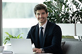 Happy businessman in formal wear using laptop and smiling