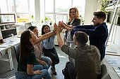 Multiracial employees team with male leader, coach giving high five.