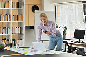 Smiling Caucasian businesswoman work on gadgets in office