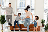 Happy family with two children jumping at home.