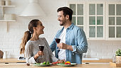 Overjoyed married couple cheering glasses of wine, laughing, having fun.