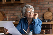 Dreamy smiling mature woman wearing glasses holding letter, reading news