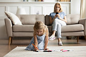 While daughter drawing seated on floor mom addicted with smartphone