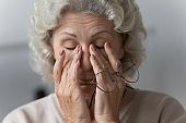 Tired mature woman rubbing nose bridge after taking off eyewear.