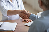 Female doctor and senior patient shake hands, close up view